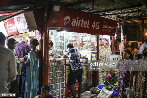 Advertisements for Bharti Airtel Ltd are displayed above customers at a mobile phone store in Mumbai India on Saturday April 21 2018 Bharti Airtel...