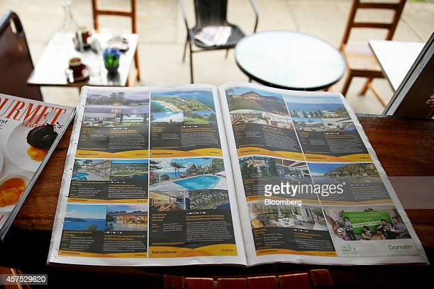 Advertisements for residential properties displayed in a newspaper sit on a bench at a cafe in the suburb of Roseville in Sydney Australia on...