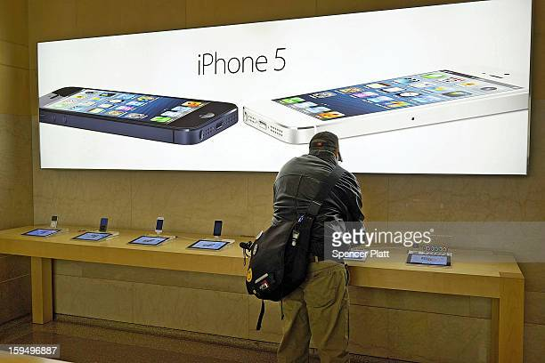 Advertisements for the iPhone 5 are displayed at an Apple store on January 14 2013 in New York City Responding to weaker than expected demand Apple...