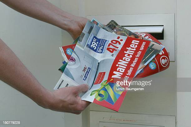 Advertising brochures throw in a letterbox Symbolic picture to the subject Flood of advertisings