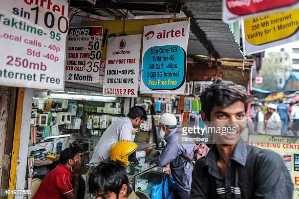 Advertisments for Bharti Airtel Ltd left to right Aircel Ltd and Vodafone India Ltd services are displayed outside a mobile phone store in Mumbai...