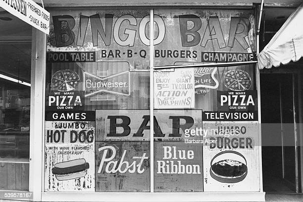 Adverts for fast food in the window of the Bingo Bar Miami Beach Florida 25th January 1981