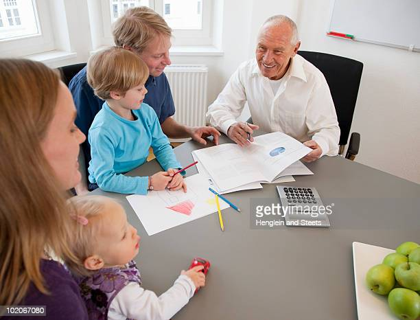 Advisor discussing papers with a family