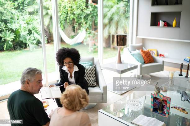 advisor showing and discussing some data with her clients - financial advisor stock pictures, royalty-free photos & images