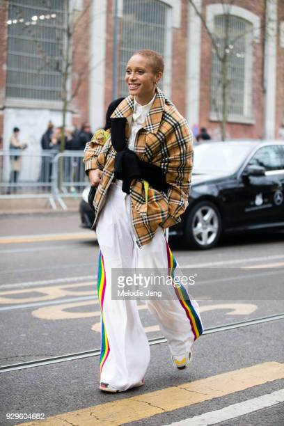 Adwoa Aboah wears a yellow Burberry check top a black sweater tied across her chest white pants with a rainbow stripe and carries a black Palace bag...