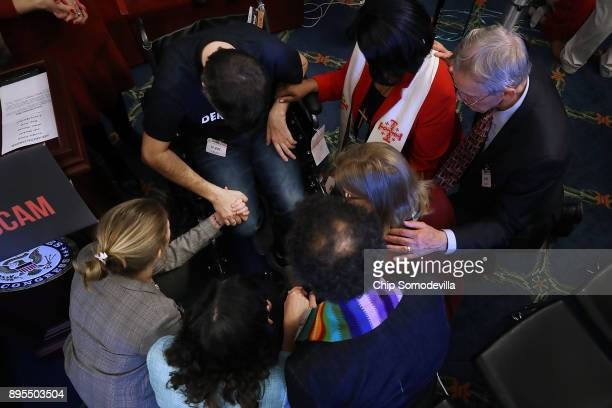 Ady Barkan who lives with Amyotrophic Lateral Sclerosis prays with faith leaders following a rally against the GOP tax bill in the Rayburn Room at...