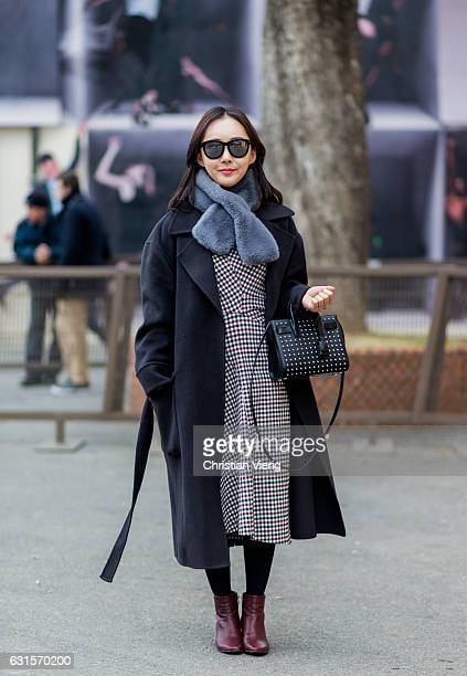 Aekyung Cho is wearing a plaid dress black bag red leather ankle boots wool coat on January 12 2017 in Florence Italy