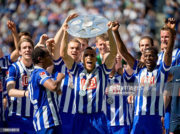 Aenis Ben-Hatira holds the trophy aloft as he celebrates with his Hertha Berlin team mates after the German second division Bundesliga football match...