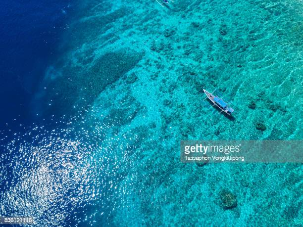aerial bird eye view of local tour small boat in coral spot blue sea