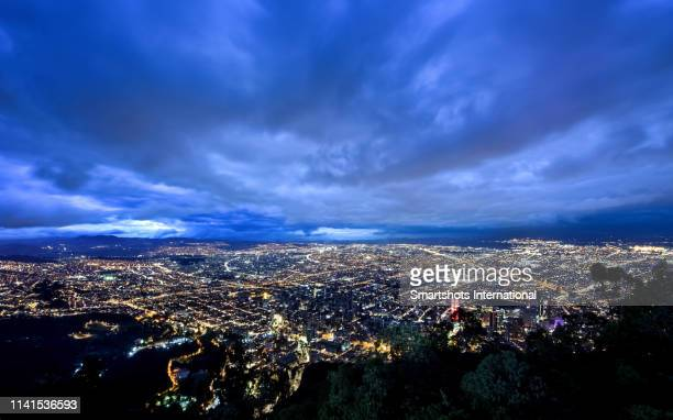 aerial city skyline illuminated at late dusk with endless city lights of urban sprawl - bogota stock pictures, royalty-free photos & images