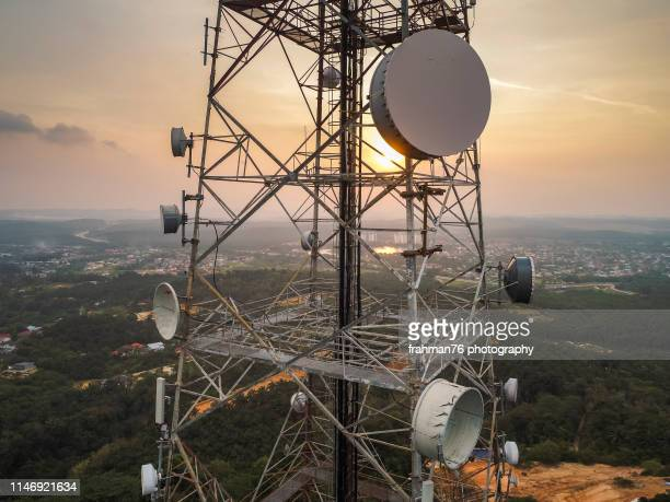 aerial close up view of telecommunication tower with huge antenna mounted on the pillar taken during sunset - tower stock pictures, royalty-free photos & images