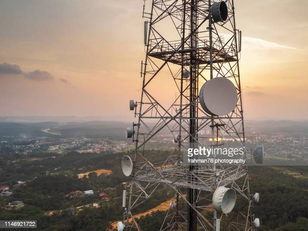 aerial close up view of telecommunication tower with huge antenna mounted on the pillar taken during sunset - communications tower stock pictures, royalty-free photos & images