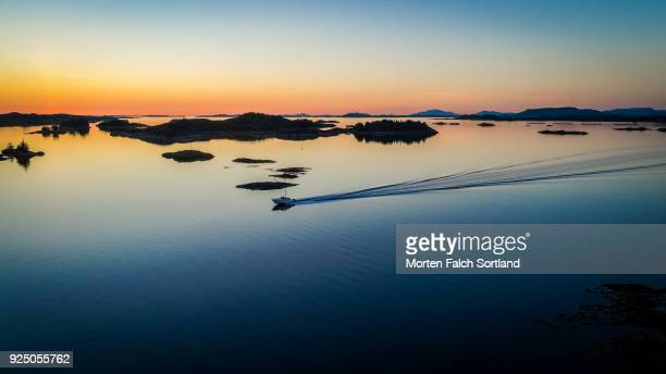 aerial drone shot of a boat sailing in still waters against a dramatic sunset in norway, summertime - hordaland county stock pictures, royalty-free photos & images