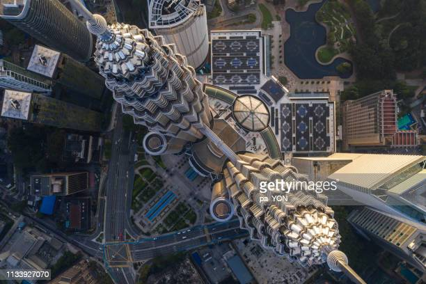 aerial drone shot of petronas tower in morning light - petronas towers stock pictures, royalty-free photos & images