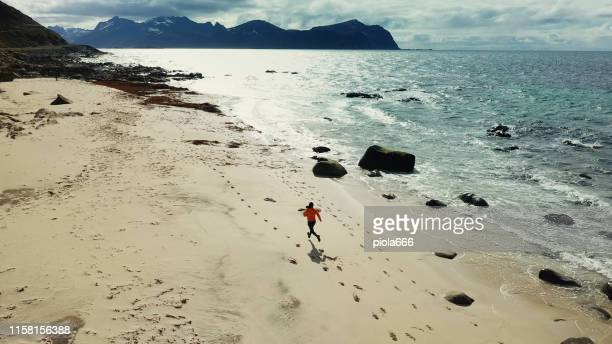 aerial drone view: man running in lofoten islands - northern norway stock pictures, royalty-free photos & images