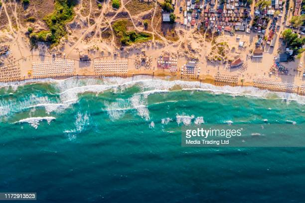 aerial drone view of a crowded beach umbrellas bars and people on the summer sand - bulgaria stock pictures, royalty-free photos & images