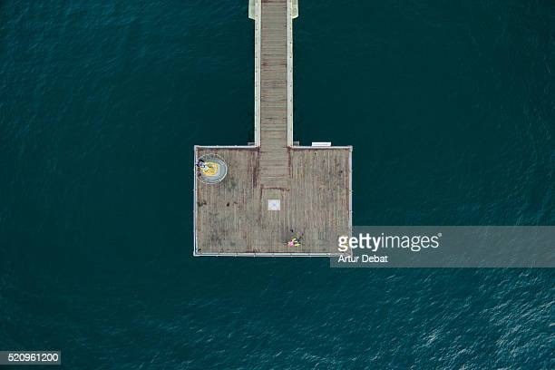 Aerial drone view of a long pedestrial walkway dock in the Mediterranean sea with beautiful blue water colors in the Catalonia region.