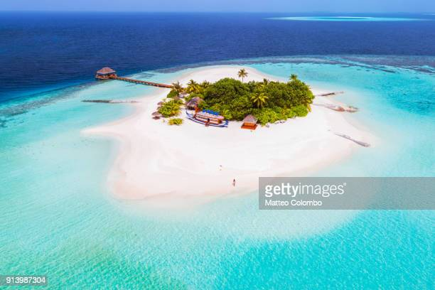 aerial drone view of a tropical island, maldives - insel stock-fotos und bilder