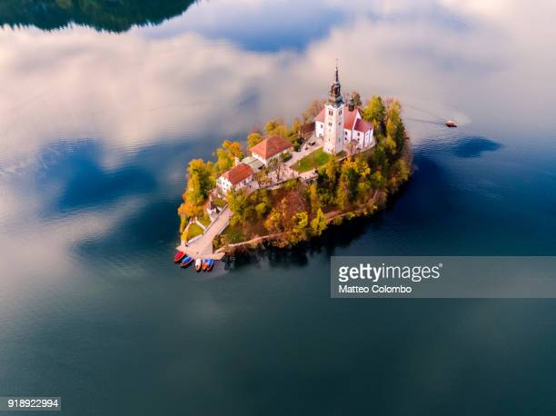 aerial drone view of bled island in autumn, slovenia - slovenia stock pictures, royalty-free photos & images