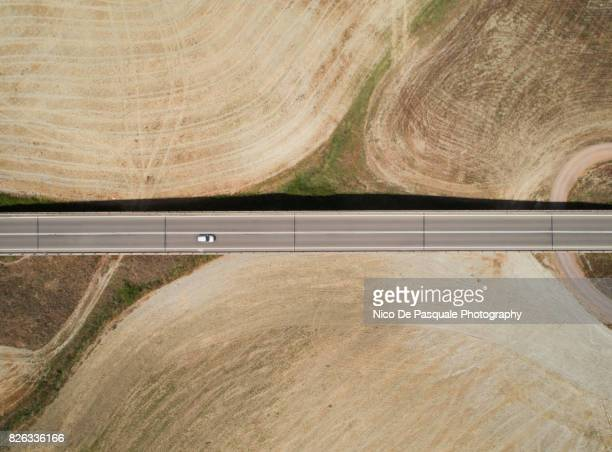 Aerial drone view of car crossing road
