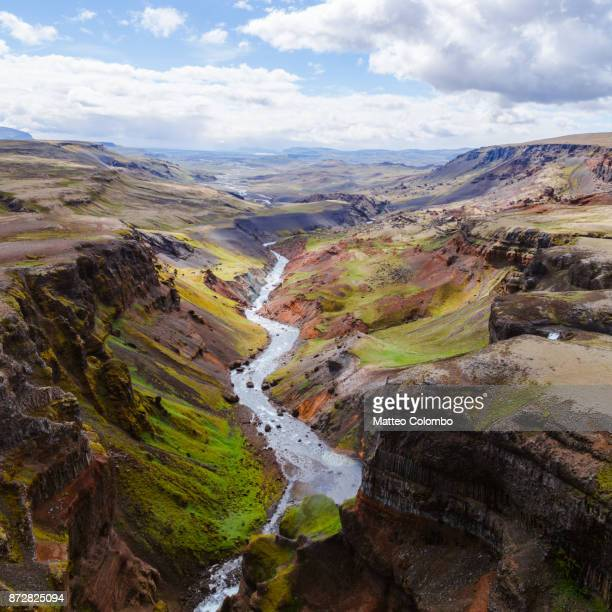 aerial drone view of river through rugged landscape, iceland - canyon foto e immagini stock