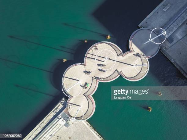 aerial drone view of the circle bridge (cirkelbroen) on the inner harbor of copenhagen, denmark. taken by drone from straight above. - brücke stock-fotos und bilder