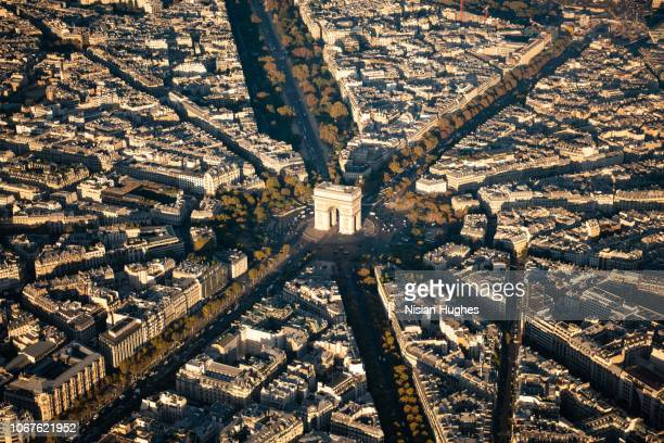 aerial flying over arc de triomphe in paris france at sunrise - place charles de gaulle paris stock photos and pictures