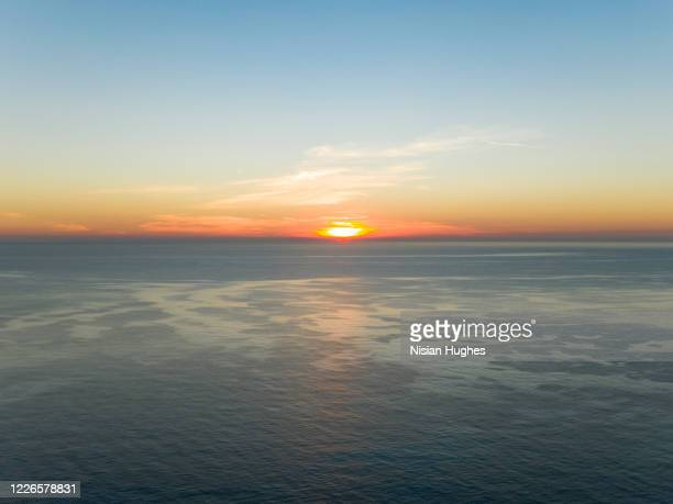aerial flying over coast of ramatuelle france looking out over sea at sun rise - var stock pictures, royalty-free photos & images