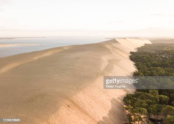 aerial flying over dune of pilat in france looking over the sand at sun rise - gironde stock pictures, royalty-free photos & images