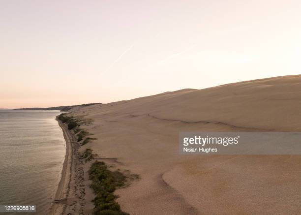 aerial flying over dune of pilat in france looking over the sand at sun rise - brown stock pictures, royalty-free photos & images