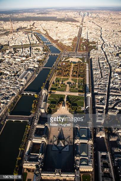 aerial flying over musée du louvre in paris france, daytime - louvre pyramid stock pictures, royalty-free photos & images
