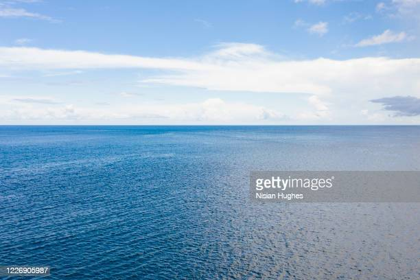 aerial flying over the ocean looking at the clear horizon in the distance - horizont über wasser stock-fotos und bilder