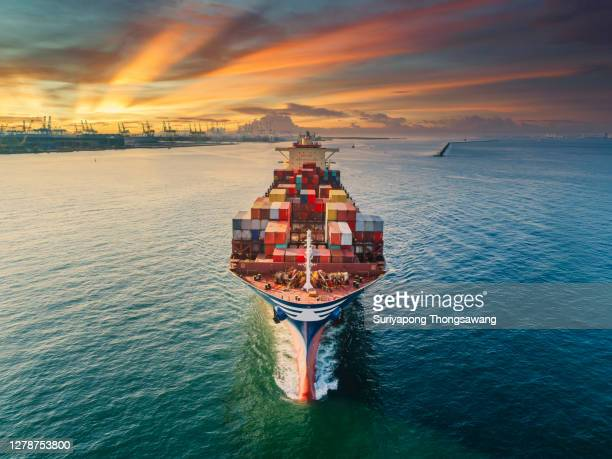 aerial front view container cargo ship full carrier container with terminal commercial port background for business logistics, import export, shipping or freight transportation. - schiffsfracht stock-fotos und bilder