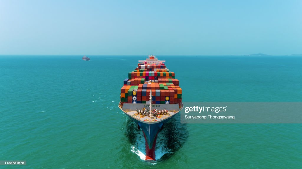 Aerial front view Container Ship full load container going to seaport or unload at container warehouse on the blue sea. Logistics, import export, shipping or transportation. : Stock Photo