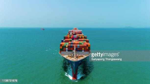aerial front view container ship full load container going to seaport or unload at container warehouse on the blue sea. logistics, import export, shipping or transportation. - ship front view stock-fotos und bilder