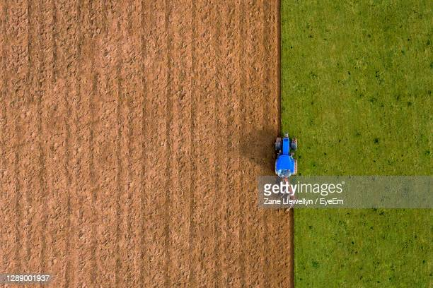 aerial high angle view of tractor ploughing field vertical line - symmetry stock pictures, royalty-free photos & images