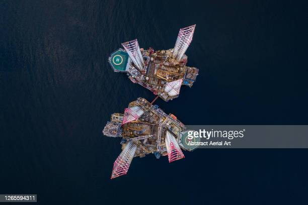 aerial image looking directly down on two offshore oil platforms, cromarty firth, scotland, united kingdom - drone stock pictures, royalty-free photos & images
