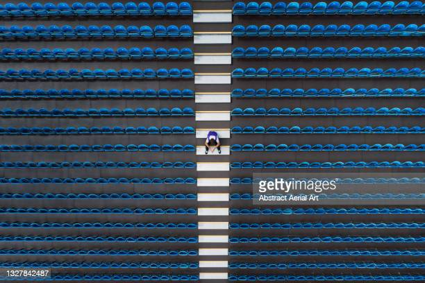 aerial image looking down on one person sitting amongst empty stadium seating, united kingdom - mid adult stock pictures, royalty-free photos & images