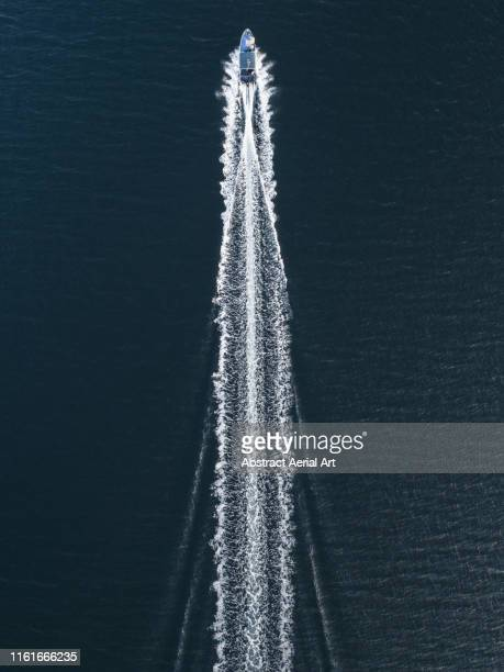 aerial image of a speed boat moving quickly across the ocean, hong kong - nautical vessel stock pictures, royalty-free photos & images