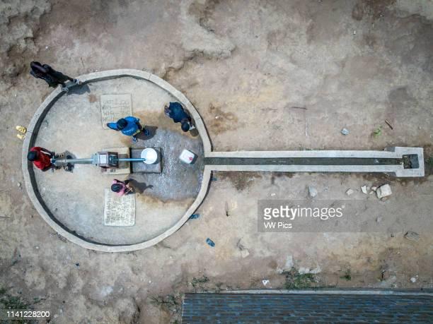 Aerial image of children pumping water at a school in Ganta, Liberia.