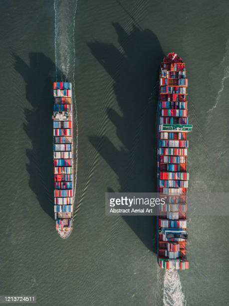 aerial image showing two cargo containers sailing passed each other, netherlands - moving past stock pictures, royalty-free photos & images