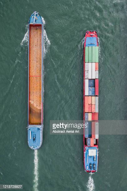 aerial image showing two industrial ships side by side in the rhine river, karlsruhe, germany - luggage hold stock pictures, royalty-free photos & images