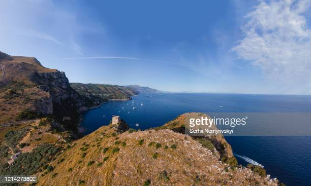 aerial landscape of nerano bay. old signal tower, fortification, rocky shores and blue sea. the city is far on the horizon. yachts and ships. water transport movement. recreation and tourism, italy - baia foto e immagini stock