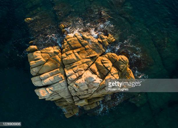aerial looking directly down on rocks surrounded by water in ramatuelle in france - var stock pictures, royalty-free photos & images