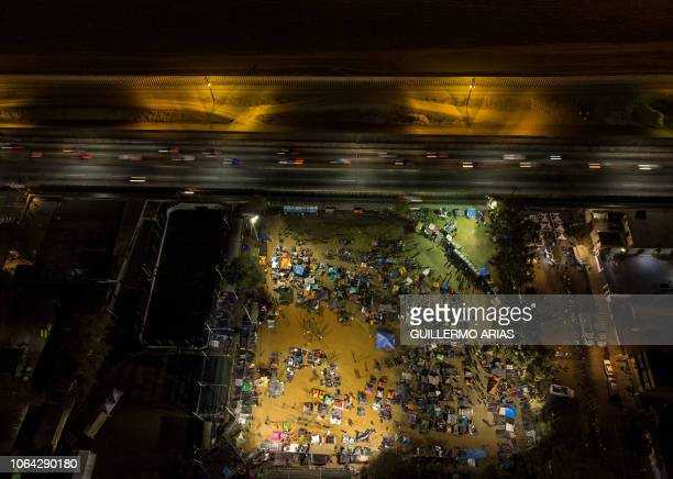 TOPSHOT Aerial night view of Central American migrants mostly from Honduras moving towards the United States camping at a makeshift shelter near the...