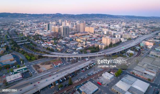 aerial: oakland city skyline at sunset. california, usa - oakland california skyline stock pictures, royalty-free photos & images