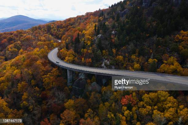 aerial of a winding highway through a forest in autumn - appalachian trail stock pictures, royalty-free photos & images