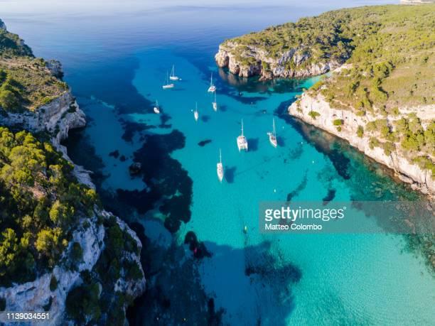 aerial of bay and yachts, cala macarella, menorca - カラマカレラ ストックフォトと画像
