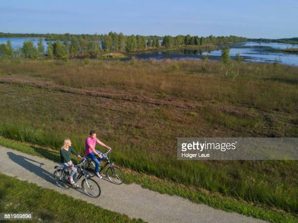 aerial of couple cycling along lakes and peat bog lands through bourtanger moor-bargerveen international nature park, near zwartemeer, drenthe, netherlands - drenthe stock pictures, royalty-free photos & images