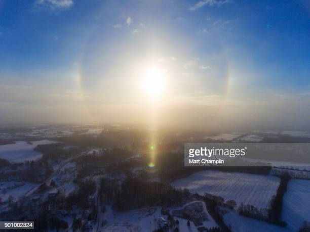 aerial of halo and sun dogs around winter sun - winter solstice stock photos and pictures